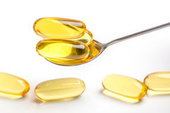Golden soft gel capsules served by spoon and blurred another cap Royalty Free Stock Photography