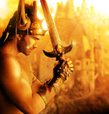 Golden soldier. Portrait of a beautiful young warrior holding sword in golden light Stock Images