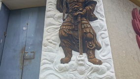 Golden Soldier Bas-Relief on White Panel of Building Wall. Closeup large golden soldier with sword on white gyps panel bas-relief on building wall in monastery stock video footage