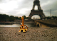 Golden souvenir - a miniature Eiffel Tower infront of the real thing Stock Image
