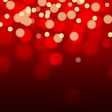 Golden sparkles on red background with bokeh effect. Stock Images