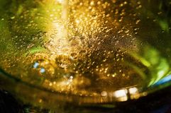 Golden sparkling bubbles of champagne wine in bottle. Luxury golden sparkling bubbles of champagne wine in green bottle, detail royalty free stock images