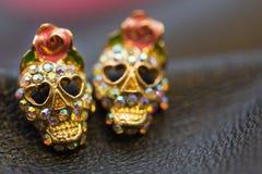 Golden sparkling earrings in the shape of smiling skulls for Helloween party. Golden sparkling earrings with rhinestones in the shape of smiling skulls for Royalty Free Stock Images