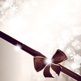 Golden sparkly holiday background with an elegant bow. Sparkly background with snowflakes and an elegant gold and brown bow. Graphics are grouped and in several Stock Images