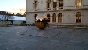 Golden sphere in front of the building stock photos