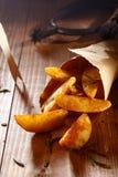Golden spicy potato wedges Stock Photos