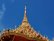Golden spire soars into blue sky. At Buddhist temple in Thailand Stock Photos