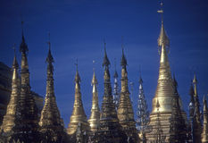 Golden spires of Buddhist stupas in temple Stock Images