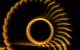 Golden Spirls and Rings of Light. Golden spirls  and rings or circles of blazing light isolated on black illusion Stock Photos