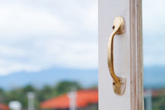 Golden Stainless steel vintage style handle on painted wooden white window Stock Image