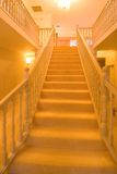 Golden Stairway. A white carpet covered internal staircase in a magnificent luxury home in Central Queensland, Australia. Warm afternoon light touches all around royalty free stock photography