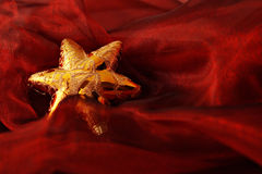 Golden star. Surrounded with red cloth Royalty Free Stock Photography