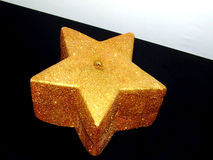 Golden star. Gold candle in a shape of a star stock photos