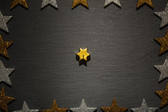 Golden star candle on slate with star frame Stock Images