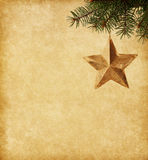 Golden star  hanging on a spruce. On paper  background Royalty Free Stock Photo