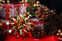 Golden star with red gift boxes and fir cones Royalty Free Stock Image