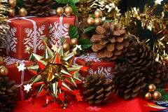 Golden star with red gift boxes and fir cones Royalty Free Stock Images