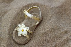 Golden star sandal buried in summer beach sand Royalty Free Stock Image