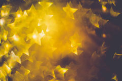 Golden Star Shaped Bokeh. Festive background with defocused golden glitters, bokeh in a shape of a star Royalty Free Stock Photography