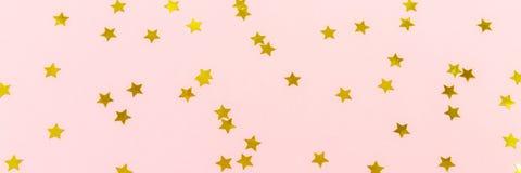 Golden star sprinkles on pink. Festive holiday background. Celeb Stock Photos