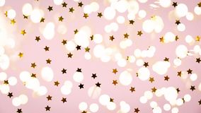 Golden star sprinkles on pink. Festive holiday background. Celebration concept. Top view, flat lay. Horizontal, wide screen format, bold light bokeh background stock photography