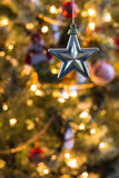 Golden star stands out against colourfully decorated Christmas in background. A decorative, five-pointed star hangs in front of a decorated Christmas tree Royalty Free Stock Images