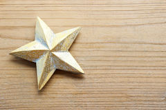 Golden star on wooden background. Stock Photo
