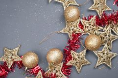 Golden stars Christmas composition decorations on a gray background with red tinsel. Golden stars Christmas composition decorations on a gray background with a royalty free stock photos