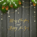 Golden stars and Christmas greeting on black wooden background. Holiday lettering Merry Christmas and Happy New Year on black wooden background with winter Royalty Free Stock Photography