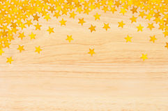 Golden stars in the form of confetti over wooden texture Stock Photography