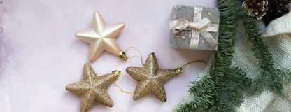 Golden stars, gift box, christmas tree branch and decorations on light pink textured background. royalty free stock photography