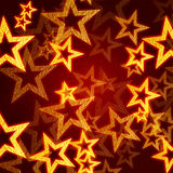 Golden stars in red background. Golden stars over red background with feather center Stock Image