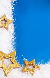 Golden stars on snowy background Stock Image