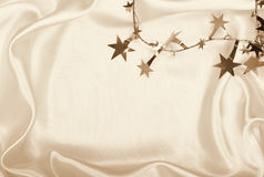Golden stars and spangles on silk as background. In Sepia toned. Stock Images