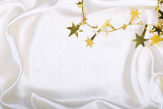 Golden stars and spangles on white silk Stock Images