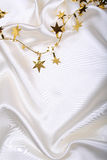 Golden stars and spangles on white silk Stock Photo