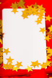 Golden stars and white card on red cloth. macro Stock Photo