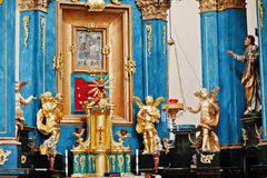 Golden statue of angels and icon of Holy Mary at iconostasis of Stock Images