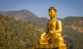 Golden Statue of Buddha. Golden Statue of Budhda with background of green forest and blue sky Stock Photos