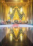 The golden statue is in the temple with a golden reflection. Royalty Free Stock Photography
