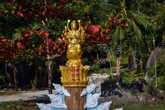 Golden statue of the goddess in the blooming garden Buddhist temple at a small Thai village Royalty Free Stock Photo