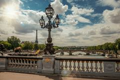 Golden statue and lighting post adorning the Alexandre III bridge over the Seine River and Eiffel Tower in Paris. stock image