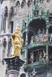 The Golden statue of Mary Mariensaule and dancing dolls of Town Hall at Marienplatz in Munich, Germany. The Golden statue of Mary Mariensaule and dancing dolls Stock Photos