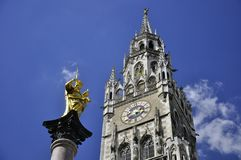 The golden statue of Mary Mariensaule with townhall tower. Stock Photos