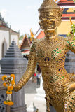 Golden statue with offering in Wat Phra Keaw, Bangkok Royalty Free Stock Photo
