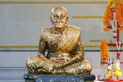 Golden statue of old Buddhist monk. Gold Covered Statue Of Buddist Monk in Bangkok, Thailand Stock Photo
