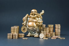 Golden statuette. Surrounded by small gold coins stock photo