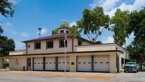A golden steer perched on the top of a small fire department building. GONZALES, TEXAS - JUNE 10 2018: the fire department building in the center of town royalty free stock image