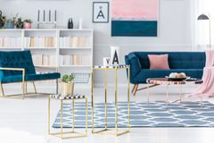 Golden stools in living room. Creative, golden stools with plant and ceramic vessels set in a living room interior with armchair and sofa in the background royalty free stock images