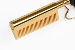 Golden Straightening Comb. A closeup view of a straightening comb, isolated on a white background stock images